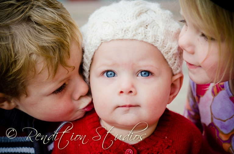 three siblings kissing